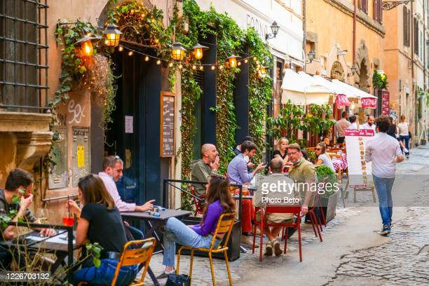 some customers enjoy an aperitif in a bar in the ancient trastevere district in rome - italy stock pictures, royalty-free photos & images