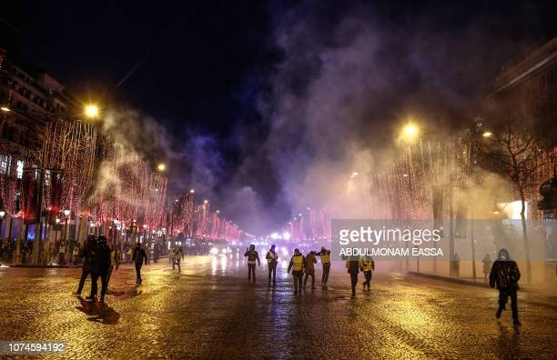 Some demonstrators of the French 'yellow vests' movement leave the Champs Elysees avenue at the end of a protest in Paris on December 22 2018 as the...