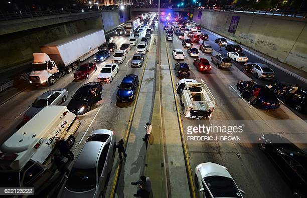 Some drivers wait outside their vehicles stuck on a shutdown freeway in downtown Los Angeles California after midnight early on November 10 2016 as...