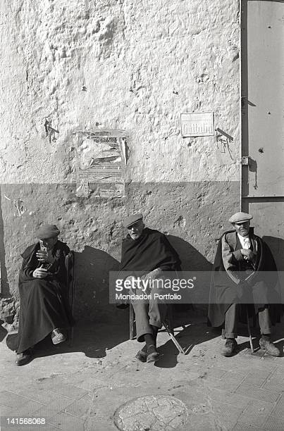 Some elderly people wearing cloaks seated along the street at San Giovanni Rotondo Italy
