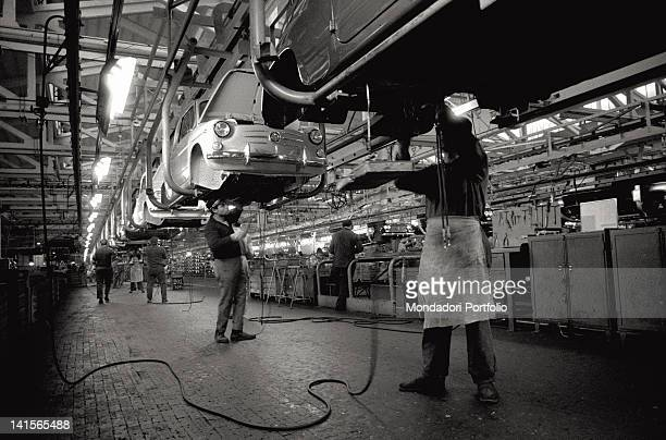 Some factory workers of FIAT Group in a warehouse They are wotking on the bodywork of a set of FIAT 1100 Turin Italy 1964