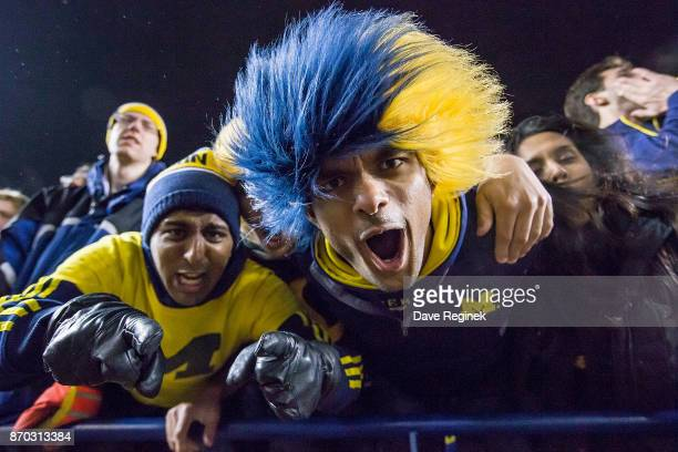Some festive Michigan fans cheer during a college football game between the Michigan Wolverines and the Minnesota Golden Gophers at Michigan Stadium...