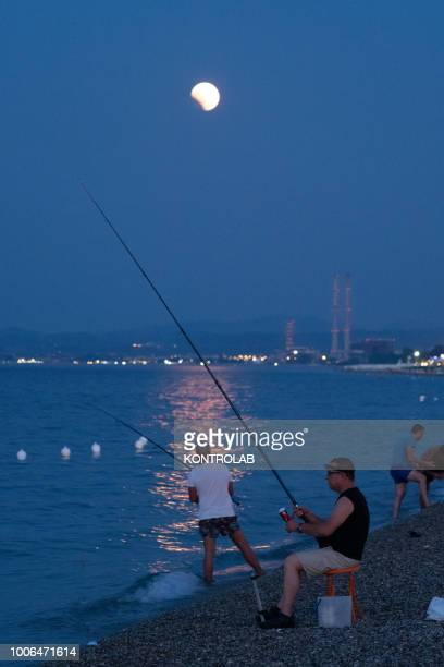Some fishermen during the total eclipse of the moon which turns red on the Ionian sea The lunar eclipse is considered the longest eclipse of the...