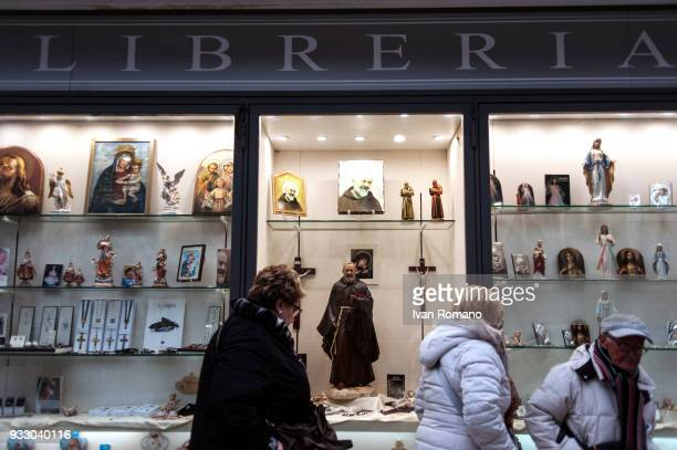 Some fithful near a gift and sacred objects shop near the Sanctuary of San Pio of Pietrelcina on March 17 2018 in San Giovanni Rotondo Italy Pope...