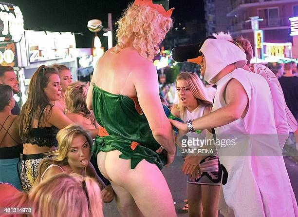 Some girls joke with a halfnaked man in Punta Ballena street in Magaluf holiday resort in Calvia on the Spanish Mallorca Island on July 19 2014 Known...