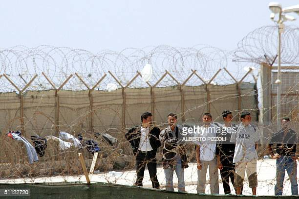 Some illegal immigrants wait behind barb wires before boarding a plane at Lampedusa airport to be sheltered in a camp near Crotone in southern Italy...
