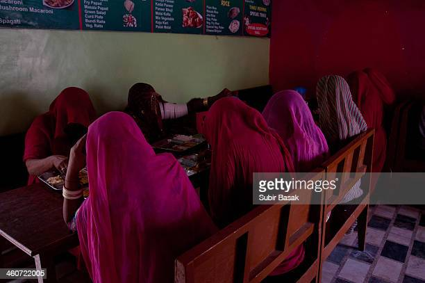 Some Indian veiled women eat lunch at a hotel,Pushkar,Rajastan,India on November 10, 2013.In India the nutrition and health status of women is...