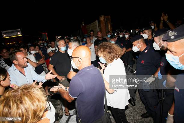 Some inhabitants of the island of Lampedusa protest in front of the port entrance against police to prevent the disembarkation of migrants on August...