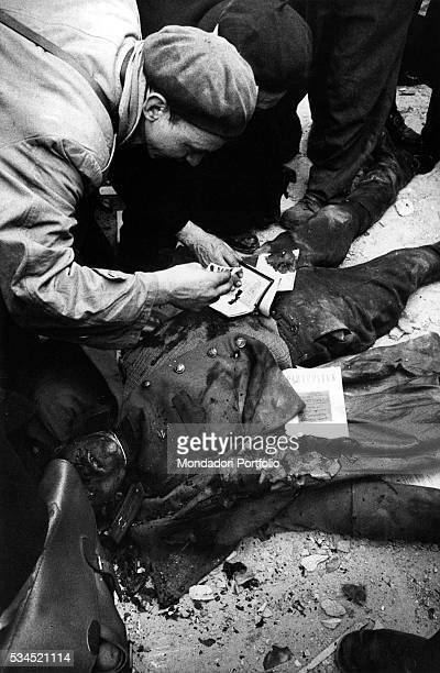 Some insurgents leafing through the documents found on the corpse of an agent of the Hungarian secret police Budapest November 1956