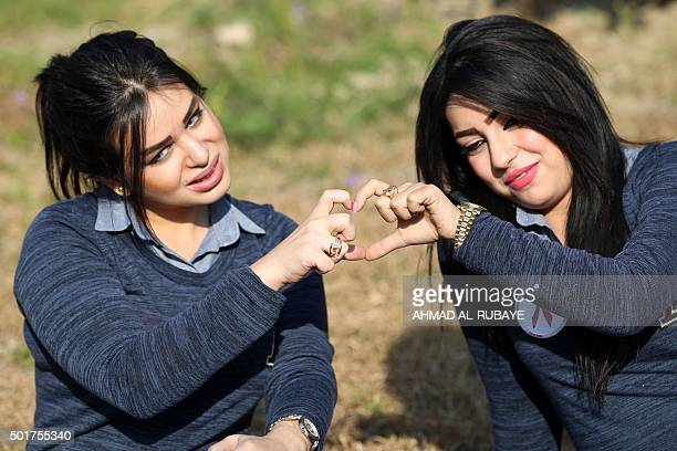 Some Iraqi candidates for Miss Iraq beauty contest shape a heaert with their fingers as they pose at the ancient archaeological site of Babylon south...