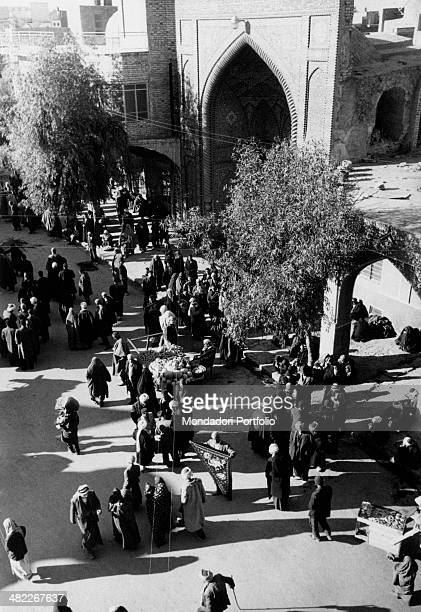 Some Iraqi people walking in front of a pointed arch portal in the Holy City Karbala December 1956