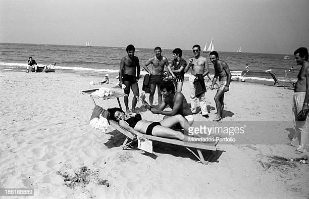 Some Italian men courting German air hostess Nicole Steigleder wearing a bikini on a deckchair A man gives her a bunch of flowers Riccione August 1964