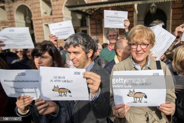 Some journalists for the flash mob hold signs of protest with the words 'Here lives a poor jackal' during the journalists' protest flash mob to...
