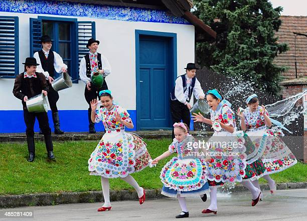 Some local school girls in traditional clothes of the Kalocsa area react as boys throw water in Kalocsa some 100 km south of Budapest on April 17...