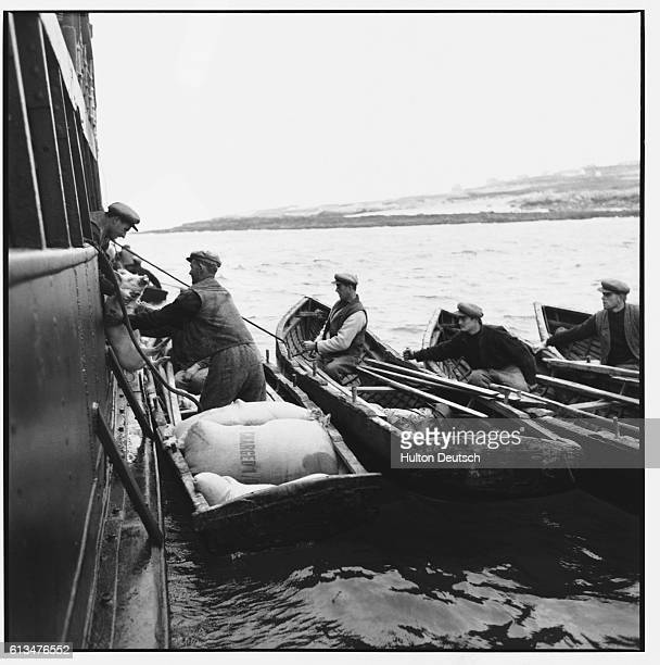 Some men of the smaller Aran Islands who have rowed out in their curraghs to a boat exchange flour for pigs