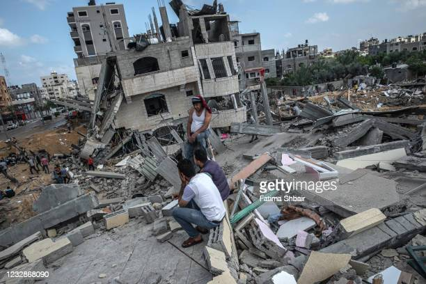 Some men sit on the rubble of a residential building in Gaza City, Gaza Strip, that was destroyed by an Israeli airstrike, on May 13, 2021 in Gaza...