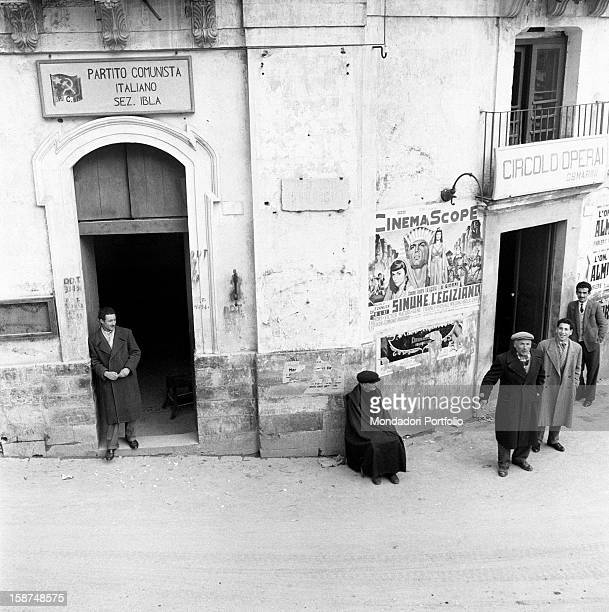 Some men standing in front of the headquarters of the Italian Communist Party and the Workers Circle in the neighbourhood called Ragusa Ibla On the...