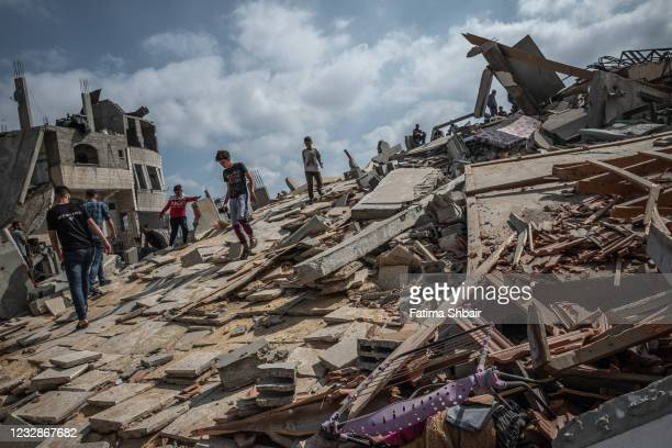 Some men walk on the rubble of a residential building in Gaza City, Gaza Strip, that was destroyed by an Israeli airstrike, on May 13, 2021 in Gaza...