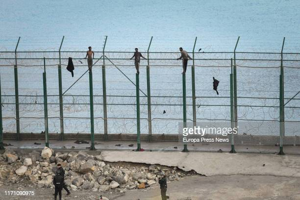Some migrants are seen jumping the fence of Ceuta while some officers of the National Police are seen waiting down at the first incursion of the year...