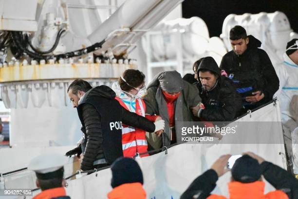 Some migrants come down from ship Diciotti helped by volunteers and the police during the landing by ship Diciotti of the Italian Coast Guard...