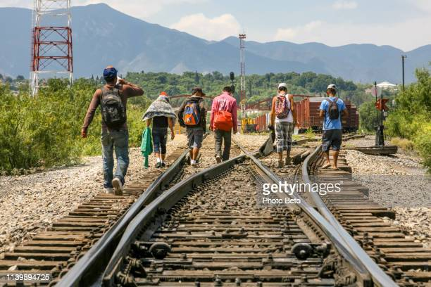 some migrants walk along the railroad near the us-mexico border in northern mexico - refugee stock pictures, royalty-free photos & images
