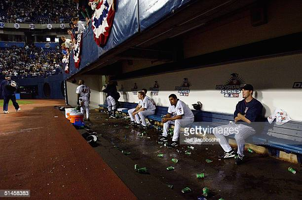 Some Minnesota Twins players sit on the bench and watch s the New York Yankees celebrate on the field after defeating the Twins during game four of...