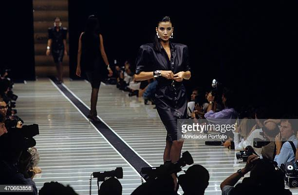 Some models walk down the catwalk presenting the new Versace collection while the photographers get ready to shoot Milan 1986