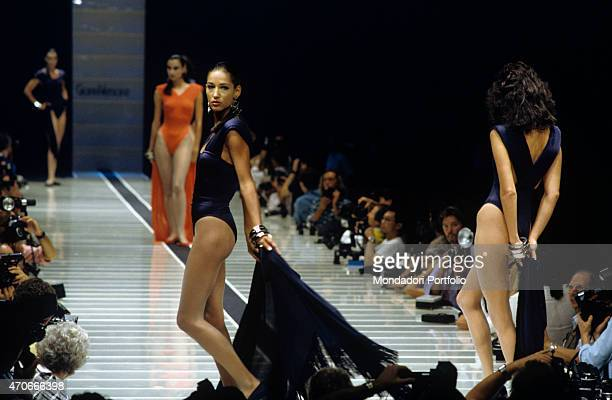 """""""Some models walk down the catwalk wearing blue and orange body suits by Armani, under the attentive look of the phographers. Milan , 1986. """""""