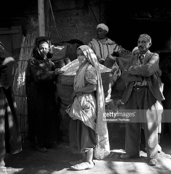 Some Moroccan labourers among them three men and a woman with the veil pose beside a large full basket in recent times in Morocco some women have...
