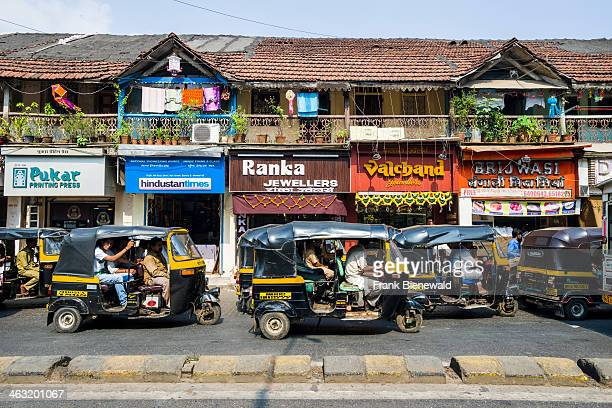 Some motor rikshaws are parking in front of a row old houses in the suburb Bandra