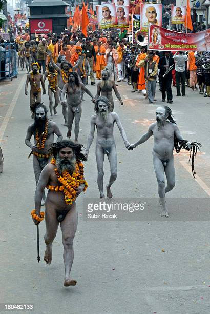 CONTENT] Some naga Sadhus or naked Hindu Holy men running in the street to take part in the holy bathe on the banks of the Ganges river on February...