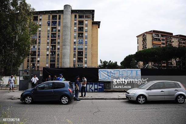 Some Napoli fans and police stand near a mourning banner dedicated to Ciro Esposito a Napoli fan died this morning displayed outside the car wash...