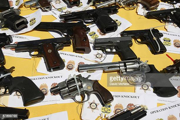 Some of about 125 weapons confiscated during what the federal authorities say is the largest gang takedown in United States history are displayed at...