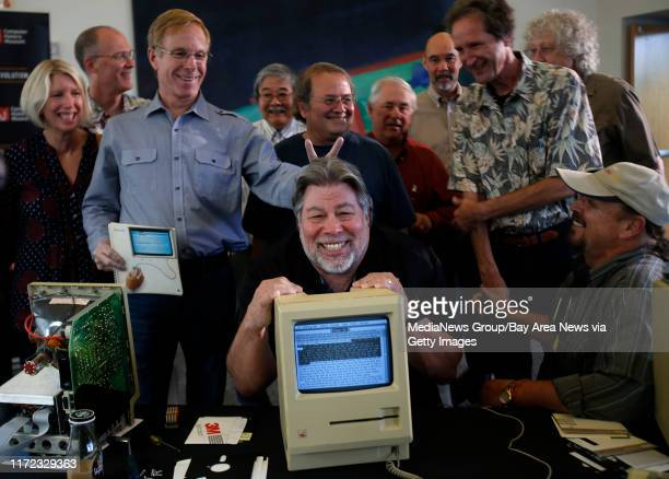 Some of Apple's earliest employees, including Steve Wozniak, center, and Randy Wigginton, left, pose for a picture with a prototype Macintosh 128K...
