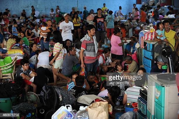 Some of more than 1500 families made homeless by a fire in a shanty town in Manila seek temporary shelter on a basketball court on January 2 2015 A...