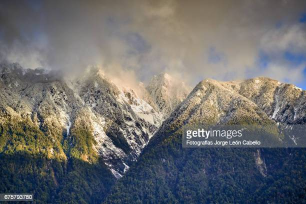 some of mountains surrounding lake todos los santos with a touch of afternoon winter sunlight - azul turquesa stockfoto's en -beelden