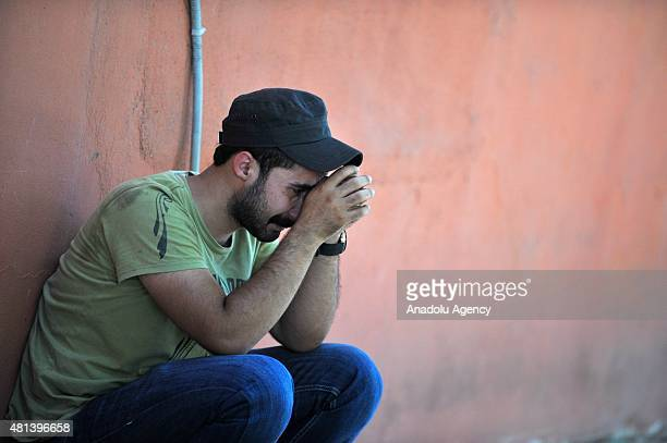 Some of people who arrive to the site of an explosion targeting a cultural center cry in Suruc district of Sanliurfa Turkey on July 20 2015 At least...