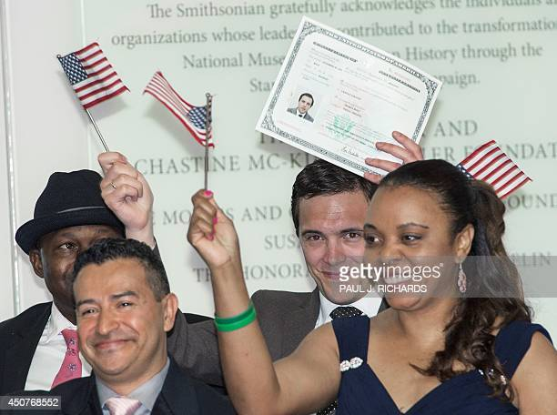 Some of the 15 newest people swornin as US citizens wave flags and a certificate of naturalization at ceremonies with designer Ralph Lauren and...