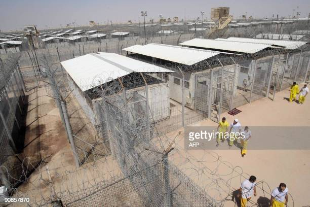 Some of the 180 high security prisoners walk in the exercise pitch at Camp Bucca on the outskirts of the southern city of Basra 550 kms from Baghdad...