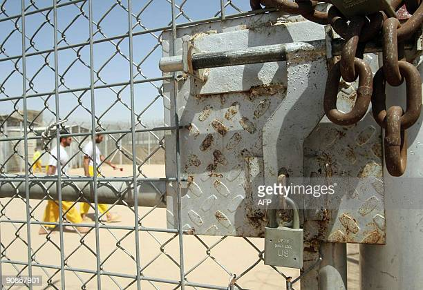 Some of the 180 high security prisoners walk past a padlocked gate as they exercise at Camp Bucca on the outskirts of the southern city of Basra 550...