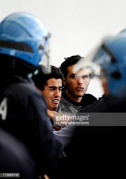 Some of the 30 Tunisian migrants kept at a Lampedusa reception center protest against their repatriation at Lampedusa airport on April 12, 2011....