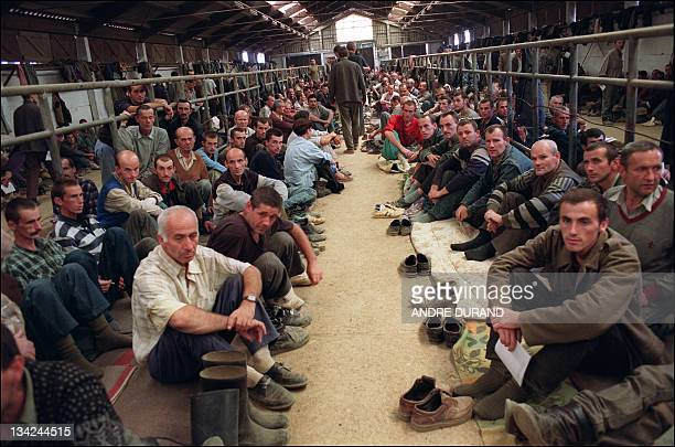 Some of the 3500 Bosnians prisoners detained in a former farm-house turned into a prison by Serbian soldiers look at the photographer 16 August 1992...