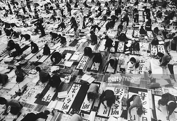 Some of the 4500 Japanese teenagers taking part in a calligraphy contest in Tokyo 12th January 1970 The given text means 'Beautiful springtime in...
