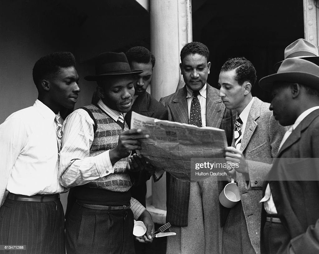 Some of the 482 Jamaicans emigrating to the UK read a newspaper on board the ex-troopship Empire Windrush which arrived at Tilbury. UK.