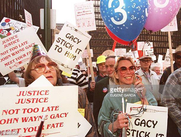 Some of the 5000 demonstrators supporting the scheduled execution of serial killer John Wayne Gacy hold balloons and wear party hats as they march in...