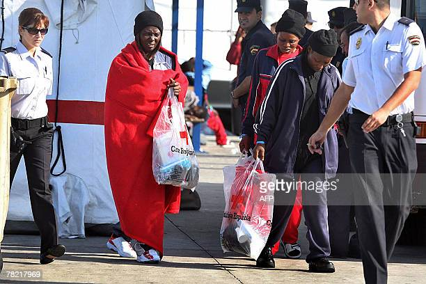 """Some of the 59 would be immigrants, who arrived on the coast of Canary island, walk escorted by policemen 03 December 2007, after their """"cayucos"""" had..."""