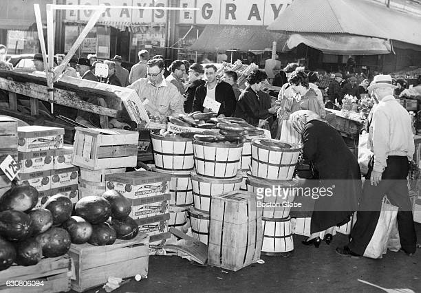 Some of the early crowd that showed up to shop for Easter flowers and fruit at stands in a Hanover Street market in Boston's North End in April...