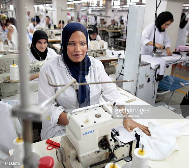 Some of the employees at their sewing machines on the factory floor at the textiles production company Sathya Clothiers which supplies clothing to...