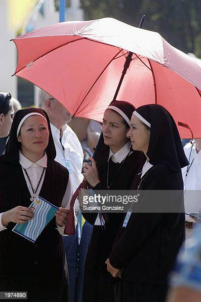 Some of the extras dressed as nuns stand under an umbrella while filming scenes of Man On Fire at a sports club May 5 2003 in Mexico City Mexico