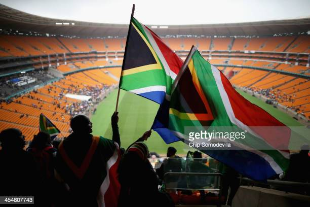 Some of the first people to arrive at the 95,000-seat FNB Stadium sing and dance before the start of the official memorial service for former South...